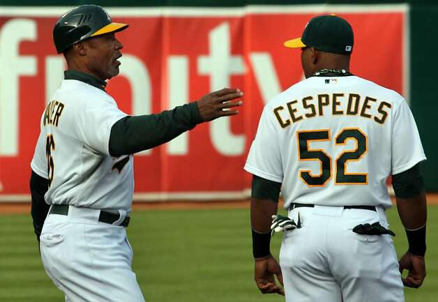 Oakland Athletics first base coach Tye Waller comunicates with spanish speaking Yoenis Cespedes through teammates that act as interpreters Saturday, April 7, 2012 at the Oakland Coliseum Calif. Photo: Lance Iversen, The Chronicle