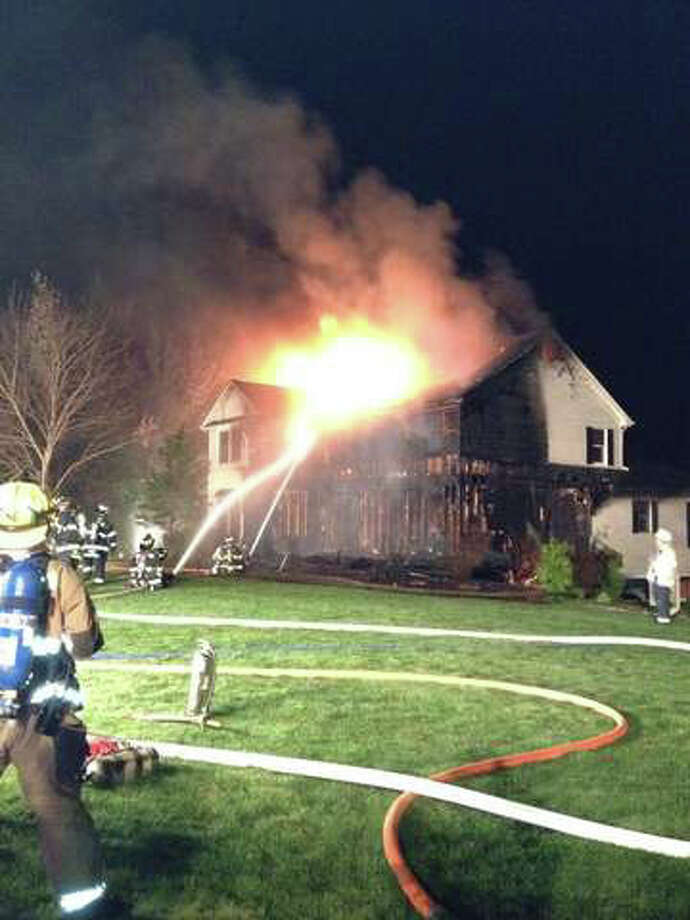 Firefighters battle a massive house fire at 18 Robin Lane in Monroe, Conn. early on the morning of Monday, April 9, 2012. Photo: WTNH Report-It