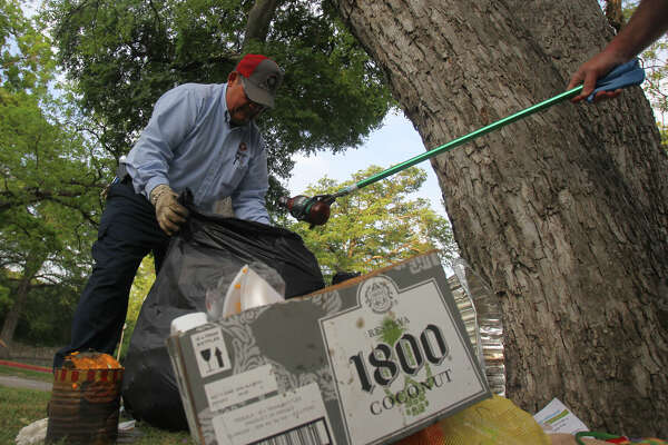 """San Antonio Parks and Recreation worker Jim Chavez (left) gathers trash as Parks and Recreation worker Mark Lawson (right) gets ready to drop a spent bottle of barbecue sauce into a bag at Brackenridge Park Monday April 9, 2012 the day after Easter celebrations. """"We try to get it all cleaned up before noon,"""" Lawson said. John Davenport/San Antonio Express-News"""