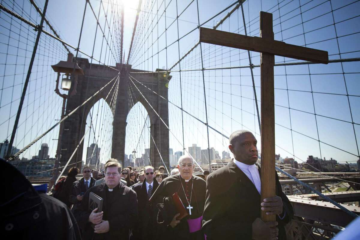 NEW YORK - APRIL 06: Worshippers lead by Rev. Richard Veras (L), Pastor at St Rita's Parish in Staten Island, The Most Rev. Nicholas DiMarzio (C), Bishop of Brooklyn, and Frank Simmonds (R), leader of New York Community of Communion & Liberation, march over the Brooklyn Bridge in the 17th Way Of The Cross procession on April 06, 2012 in New York City. The traditional Catholic procession on Good Friday recalls the crucifixion of Jesus Christ ahead of Sunday's Easter holiday. (Photo by Michael Nagle/Getty Images) *** BESTPIX ***