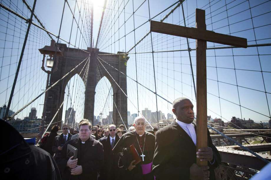 NEW YORK - APRIL 06: Worshippers lead by Rev. Richard Veras (L), Pastor at St Rita's Parish in Staten Island, The Most Rev. Nicholas DiMarzio (C), Bishop of Brooklyn, and Frank Simmonds (R), leader of New York Community of Communion & Liberation, march over the Brooklyn Bridge in the 17th Way Of The Cross procession on April 06, 2012 in New York City. The traditional Catholic procession on Good Friday recalls the crucifixion of Jesus Christ ahead of Sunday's Easter holiday. (Photo by Michael Nagle/Getty Images)  *** BESTPIX *** Photo: Michael Nagle, Getty Images / 2012 Getty Images