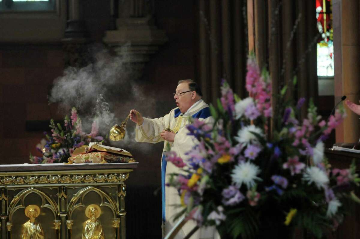 The Rev. William Pape, background at the altar, the rector at the Cathedral of the Immaculate Conception, leads Easter mass at the cathedral on Sunday, April 8, 2012 in Albany, NY. (Paul Buckowski / Times Union)