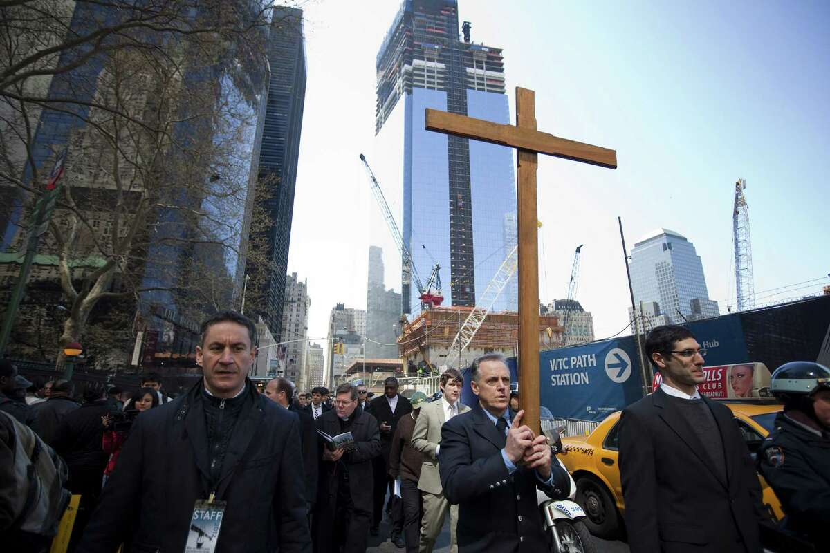 NEW YORK - APRIL 06: John Bartlett, a firefighter from Staten Island's Engine 167, carries the cross past Ground Zero in the 17th Way Of The Cross procession on April 06, 2012 in New York City. The traditional Catholic procession on Good Friday recalls the crucifixion of Jesus Christ ahead of Sunday's Easter holiday.