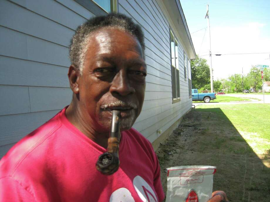 John Owens relaxes with a pipe after sweeping up the sidewalk along his house at Southerland and Pradice streets. Dan Wallach/The Enterprise Photo: Dan Wallach