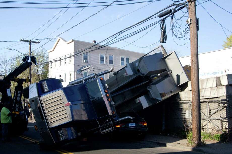 Traffic around Greenwich Avenue was snarled for almost two hours Monday morning after a dump truck got tangled in power and telephone wires and rolled over on top of a parked car. Police said the accident took place at about 7:20 a.m., when a dump truck operated by JCM Equipment Maintenance was pulling out of a driveway onto Greenwich Avenue. Photo: Chuck Knox