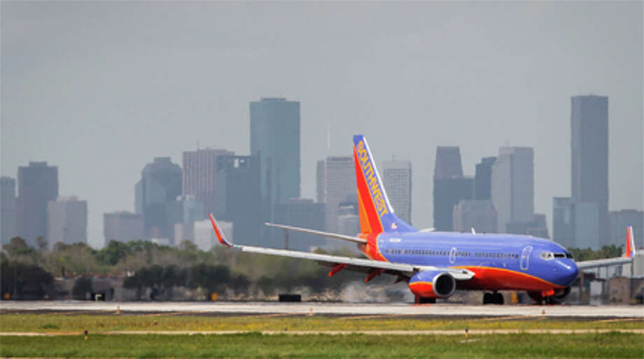 A Southwest Airlines airplane lands at Hobby Airport in front of the Downtown Houston Skyline, Friday, March 16, 2012, in Houston. Photo: ( Michael Paulsen / Houston Chronicle )