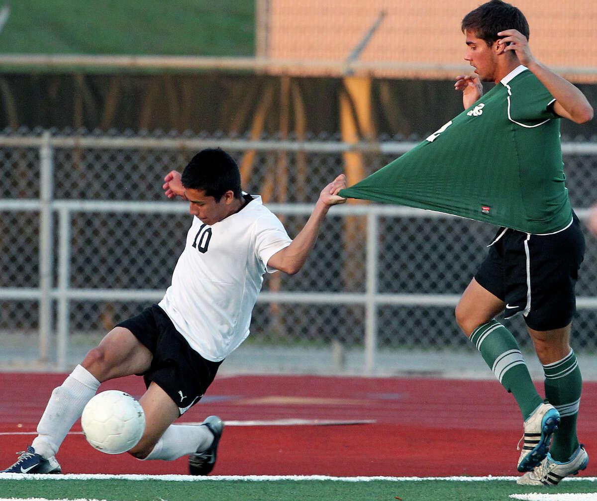 Clark's Jair Rodriguez tries to keep himself inbounds against Reagan's Davis Olson as Reagan plays Clark in boys soccer playoff action April 5 at Comalander Stadium.