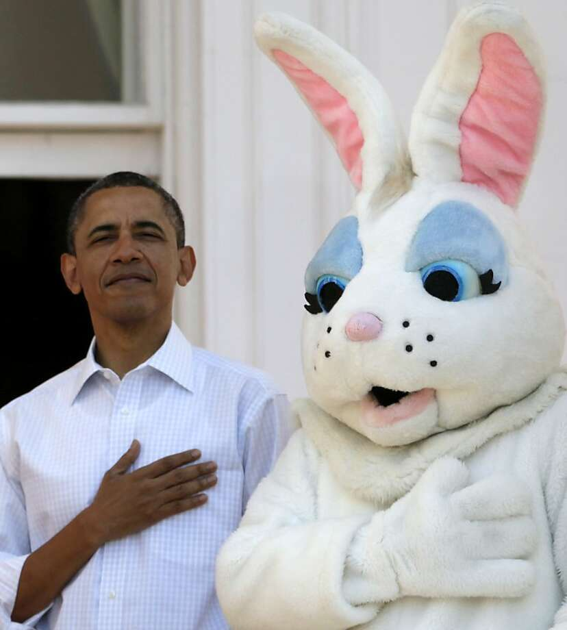 President Barack Obama stands next to the Easter Bunny during the singing of the National Anthem, at the White House in Washington, Monday, April 9, 2012, during the annual Easter Egg Roll. (AP Photo/Carolyn Kaster) Photo: Carolyn Kaster, Associated Press
