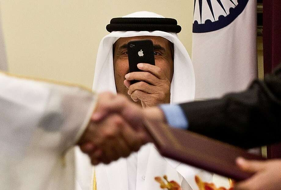 Like Mark Zuckerberg, I love Instagram too! Emir of the State of Qatar Sheikh Hamad Bin Khalifa Al-Thani takes iPhone pictures as his minister of state for foreign affairs exchanges documents and a handshake with India's human resource development minister in New Delhi. Photo: Prakash Singh, AFP/Getty Images