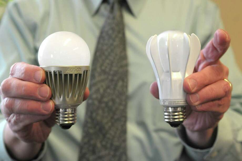 Bob Karlicek, Jr., professor and director of the Smart Lighting Engineering Research Center at RPI, holds two LED light bulbs in his office on Monday, April 9, 2012 in Troy, NY.  The bulb on the left is from Seoul Semiconductor and the one on the right is from General Electric.  (Paul Buckowski / Times Union) Photo: Paul Buckowski