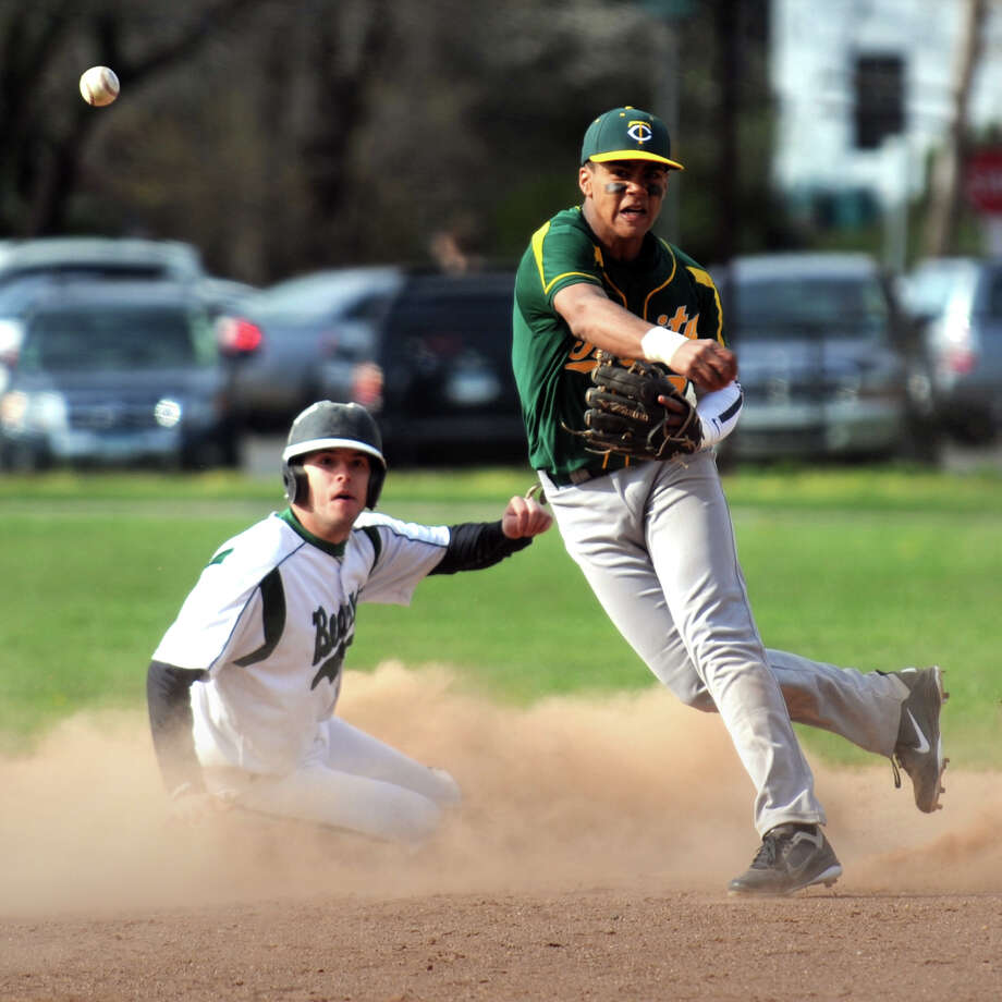 Trinity Catholic short stop Randy Polonia turns a double play in front of Norwalk's Rich Henderson during high school baseball action at City Hall Field, in Norwalk, Conn. Monday, April 9th, 2012 Photo: Ned Gerard / Connecticut Post
