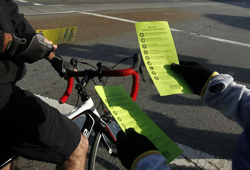A volunteer from the San Francisco Bicycle Coalition distributes the organization's Rules of the Road to cyclists commuting on Market Street in San Francisco, Calif. on Friday, April 6, 2012.