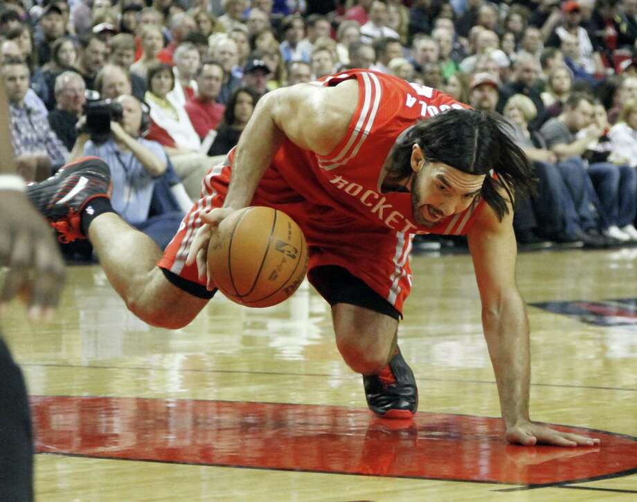 Houston Rockets forward Luis Scola, from Argentina,  tries to control the ball as he falls from being fouled during the first quarter of their NBA basketball game against the Portland Trail Blazers in Portland, Ore., Monday, April 9, 2012.(AP Photo/Don Ryan) Photo: Don Ryan, Associated Press / AP