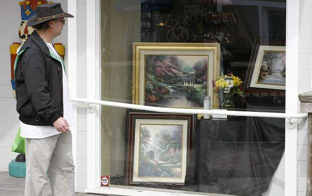 Bill Starritt takes a look at the memorial window for Thomas Kinkade. A window at the Seasons gift store at Pier 39 displayed art work in memory  of Thomas Kinkade. Photo: Sean Culligan, The Chronicle