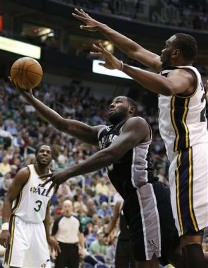 San Antonio Spurs forward DeJuan Blair, left, takes a shot while defended by Utah Jazz center Al Jefferson during the first half of an NBA basketball game Monday, April 9, 2012, in Salt Lake City. (AP Photo/Jim Urquhart) (AP)