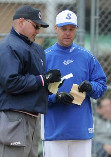 Shaker coach Steve Frank discusses a lineup change with the home plate umpire during a baseball game