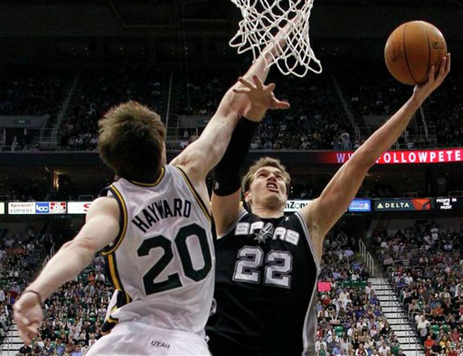 San Antonio Spurs center Tiago Splitter (22) attempts a shot while defended by Utah Jazz guard Gordon Hayward during the second half of an NBA basketball game Monday, April 9, 2012, in Salt Lake City. The Jazz won 91-84. (AP Photo/Jim Urquhart) (AP)