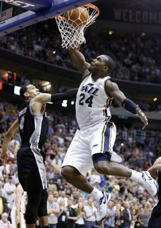 Utah Jazz forward Paul Millsap (24) dunks in front of San Antonio Spurs guard Daniel Green (4) during the second half of an NBA basketball game Monday, April 9, 2012, in Salt Lake City. The Jazz won 91-84. (AP Photo/Jim Urquhart) (AP)