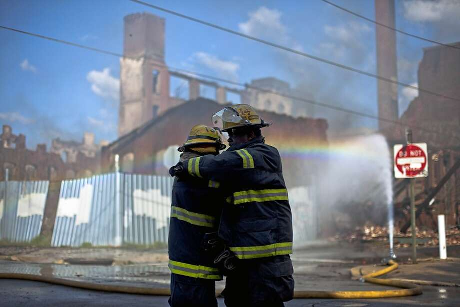 Firefighters greet each other in the aftermath of a fire in a warehouse on York Street near Kensington Avenue in Philadelphia on Monday, April 9, 2012. Two firefighters died after a wall collapsed on them while they fought the massive early-morning blaze. (AP Photo/Matt Rourke) Photo: Matt Rourke, Associated Press