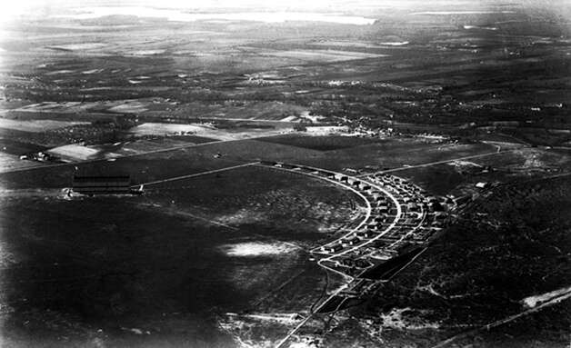 "This aerial photo taken in 1924 shows a row of World War I hangars built at Brooks Field in 1918. According to the 1970 statement nominating Hangar 9 as a national landmark, the 16 hangars formed a ""segmental arc flanking the north side of a northeast-southwest dirt runway."" Photo: Courtesy Photo, Brooks Development Authority"