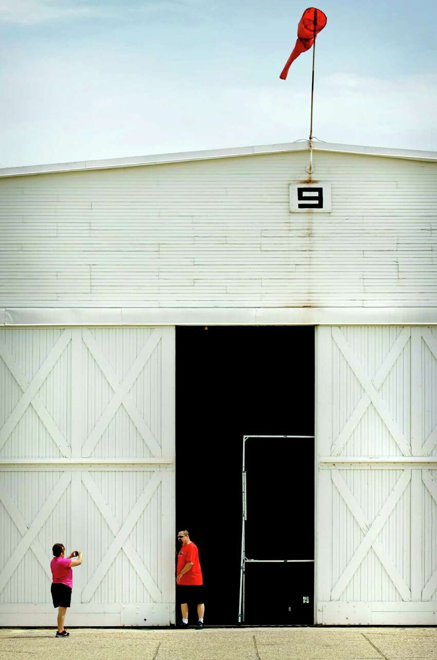 As the windsock flutters in the breeze, Yvette Bagley (left) takes a picture of her husband James Bagley, pushing the huge rolling doors on the historic Hangar 9 following Brooks City-Base Historic Hangar 9 Preservation Presentation. Officials discussed efforts to save and rehabilitate the only remaining World War I hangar at the former military base. Monday, April 9, 2012. James, who has lived on the South Side all his life, wanted to show his wife the WWI hangar because her father, who is in bad health, worked at NASA.