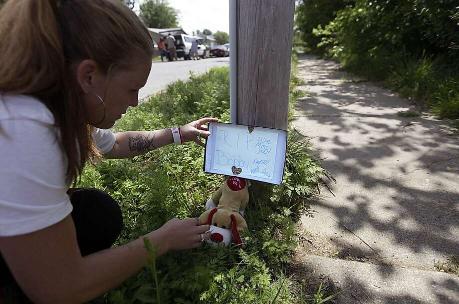 Krystal Tattershall places a memorial at the scene of her neighbor Bobby Clark's shooting at 300 W 63 Street North in Tulsa, Okla. Monday, April 9, 2012. Two Oklahoma men suspected in the shooting rampage that left Clark and two others dead, and terrorized Tulsa's African-American community, appeared in court Monday and had bond set at more than $9 million each. (AP Photo/Tulsa World, Mike Simons) Photo: Mike Simons, Associated Press