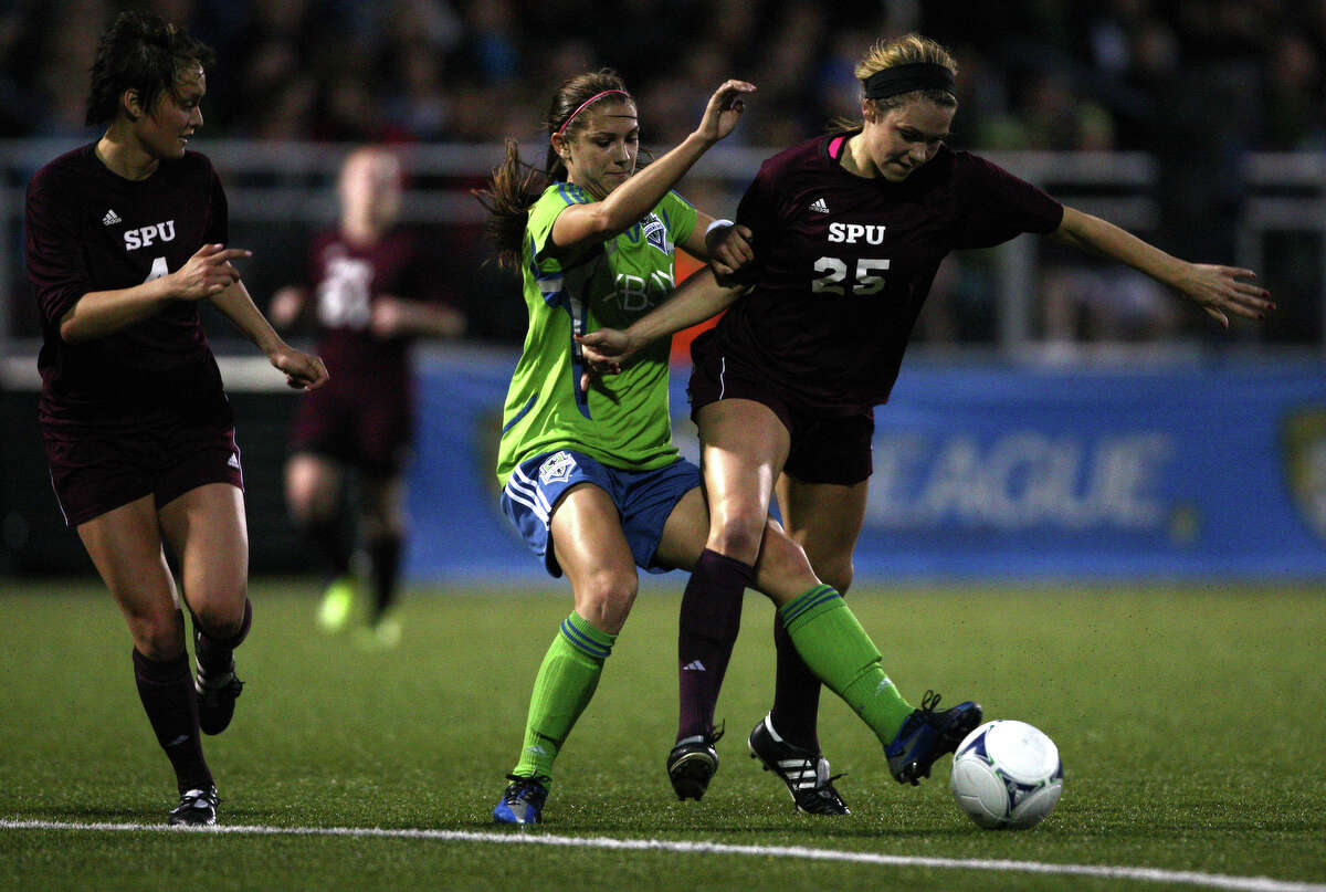 Seattle Sounders women player Alex Morgan takes the ball from Seattle Pacific University player Brittany Langdon during the Sounders women season opener on Monday, April 9, 2012 at Starfire Sports Stadium in Tukwila.