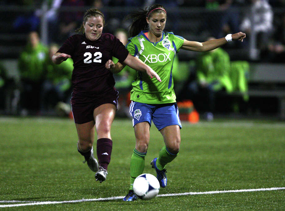 Seattle Sounders women player Alex Morgan works the ball downfield as Seattle Pacific University player Kendyl Prosser gives chase on Monday, April 9, 2012 at Starfire Sports Stadium in Tukwila. Photo: JOSHUA TRUJILLO / SEATTLEPI.COM