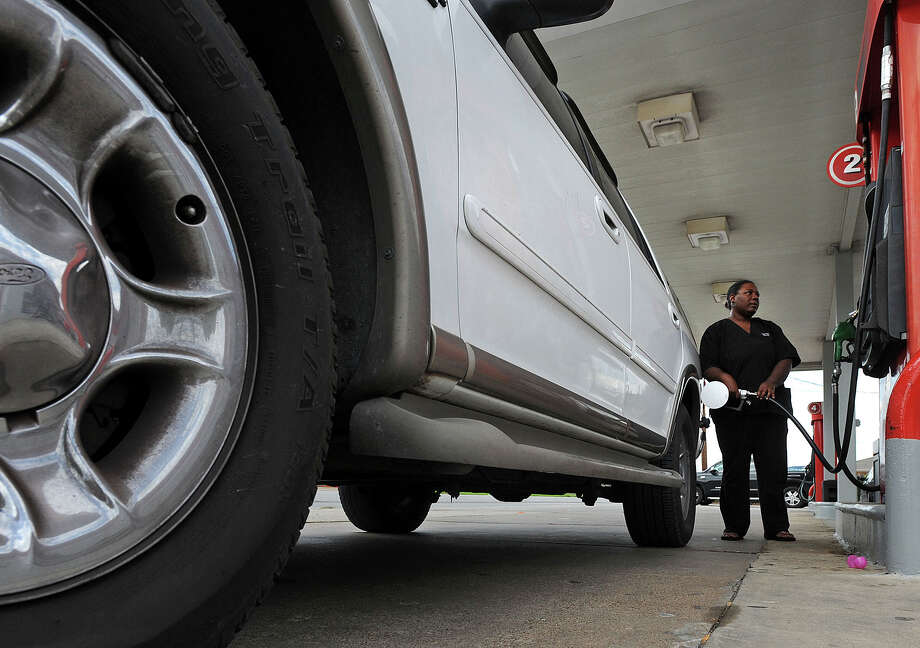 Balancia Brumley watches the numbers increase as she fills her SUV at an 11th Street gas station in Beaumont on Monday. A massage therapy student, Brumley said she is looking to trade in her large vehicle for a more economical one. Photo taken Monday, April 9, 2012 Guiseppe Barranco/The Enterprise Photo: Guiseppe Barranco, STAFF PHOTOGRAPHER / The Beaumont Enterprise