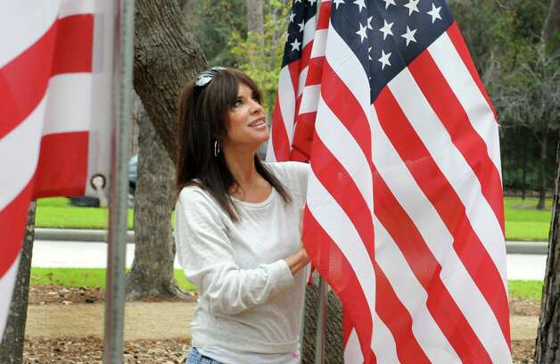Nonprofit organization president Cheryl Whitfield, of Spring, fixes a flag at the site of the proposed Fallen Warriors Memorial on Cutten Road south of Cypresswood. The flags outline the area of the proposed monument. Photo: David Hopper / freelance