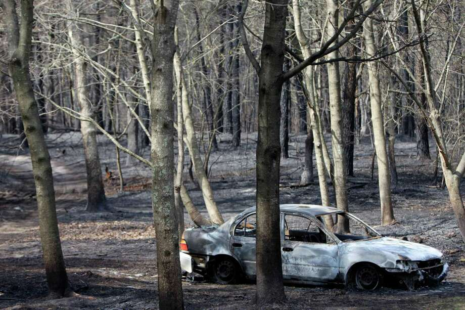 The remains of a charred car sits in the woods where a brush fire burned near Manorville, N.Y., Tuesday, April 10, 2012.  The fire, which destroyed three homes and a commercial building and burned about 1,000 acres on eastern Long Island, was nearly contained Tuesday, but officials warned that high winds could make the blaze unpredictable. (AP Photo/Seth Wenig) Photo: Seth Wenig, Associated Press / AP