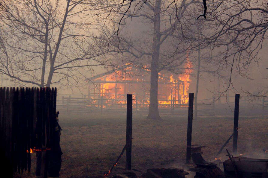 Flames consume a Suffolk County New York barn as a roaring brush fire threatens homes and commercial
