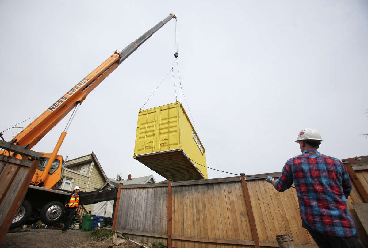 Peter Secan with HyBrid Architecture guides a cargo container home as it is craned into place on Tuesday, April 10, 2012 in Seattle's Wallingford neighborhood. The small and efficient home was placed in the back yard of a home where it will be a guest house.