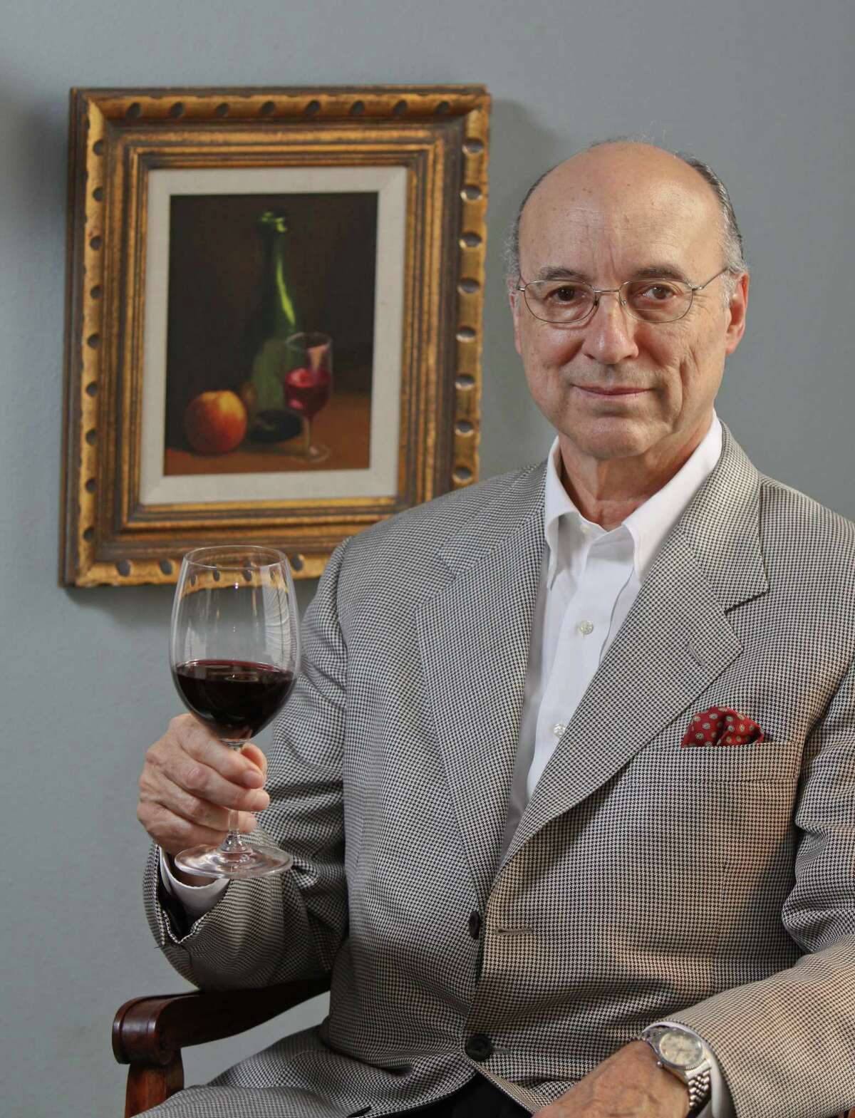 (For the Chronicle/Gary Fountain, April 4, 2012) Denman Moody enoying a glass of wine. He is sitting by a oil painting by his wife, painted prior to their meeting each other.