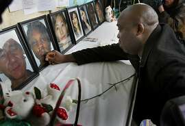 Efanye Chibuko reached out to a portrait of his slain wife Doris Chibuko during a flower ceremony at the memorial. A memorial service was held in the rain for the seven victims of Oikos University at the campus where the shooting occurred in Oakland, Calif. Tuesday April 10, 2012.