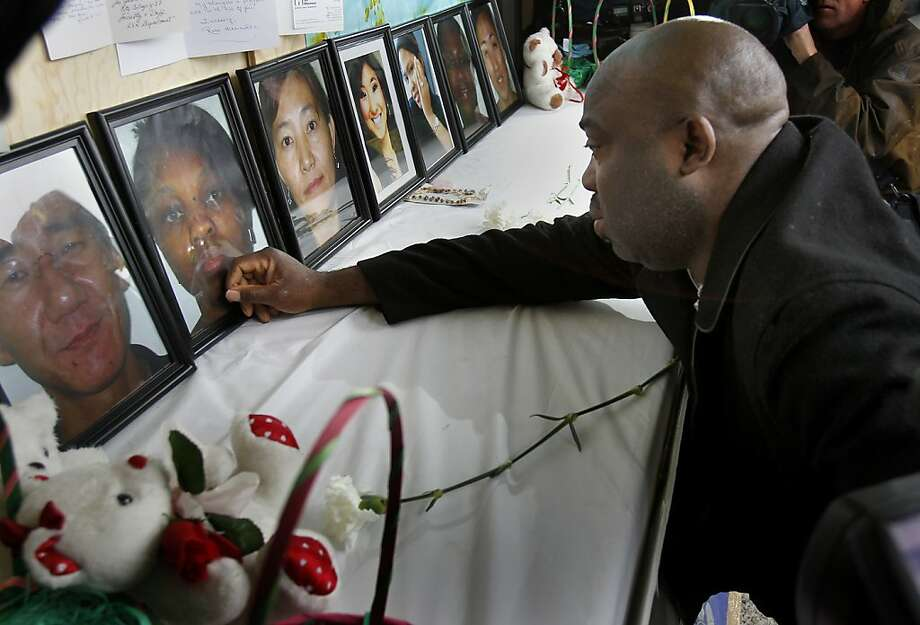 Efanye Chibuko gazes at a portrait of his slain wife, Doris, at a memorial for victims of April's Oikos University shootings. Photo: Brant Ward, The Chronicle