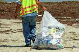 Carlos Cortez carries a bag of garbage up the beach while picking up trash left from a massive weekend beach party Tuesday, April 10, 2012, in Surfside. The city of Surfside plans to sue the organizers of the party that left a huge mess on the beach.