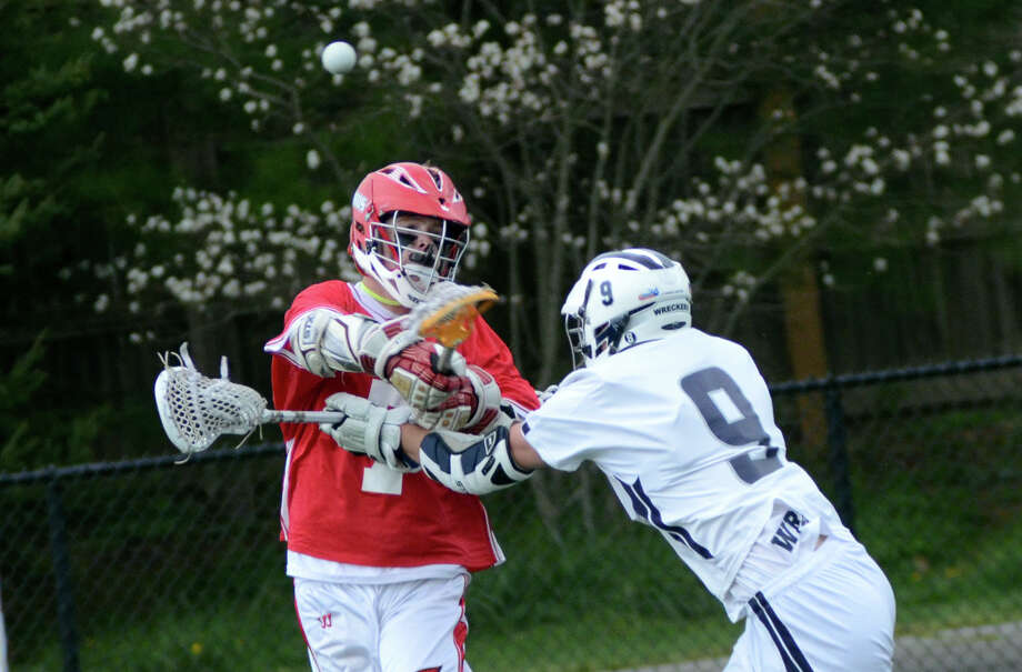 Greenwich's Chase Koorbusch (7) takes a shot on goal as Staples' Jared Levi (9) defends during the high school boys lacrosse game at Wakeman Field in Westport on Tuesday, Apr. 10, 2012. Photo: Amy Mortensen / Connecticut Post Freelance