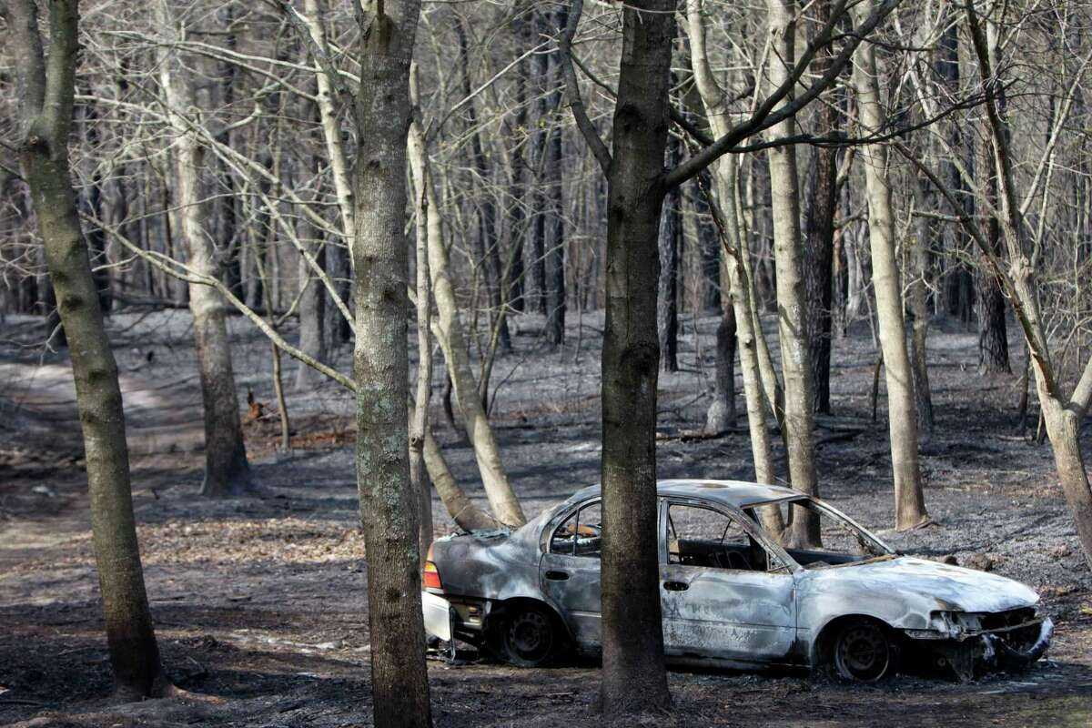 The remains of a charred car sits in the woods where a brush fire burned near Manorville, N.Y., Tuesday, April 10, 2012. The fire, which destroyed three homes and a commercial building and burned about 1,000 acres on eastern Long Island, was nearly contained Tuesday, but officials warned that high winds could make the blaze unpredictable. (AP Photo/Seth Wenig)