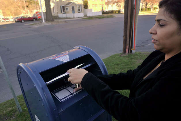 "Oksana Sanchez mails a letter on Main Street using one of the few remaining collection boxes left in Danbury on Friday, April 6, 2012. Sanchez said of the postal box ""We need it 'cause you don't want to drive all the way to downtown."" And if the post office on Main Street closes and the only remaining location is on Backus Avenue, she says, ""I don't want to drive all the way there, either."" Photo: Jason Rearick / The News-Times"