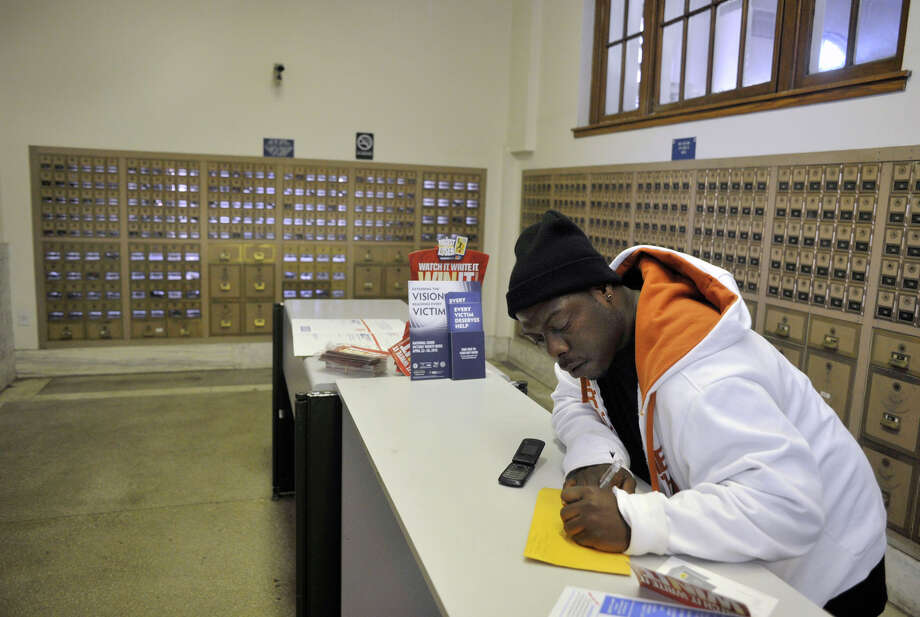 Girard Johnson prepares to mail a package in the downtown Danbury post office on Tuesday, April 10, 2012. The post office is in danger of being closed. Photo: Jason Rearick / The News-Times