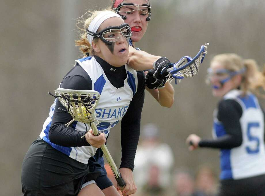 Shaker High School girls lacrosse player Maddie Devine, left, makes a run at the goal for a score during their game against Saratoga Springs High School on Tuesday, April 10, 2012 in Latham, NY.   (Paul Buckowski / Times Union) Photo: Paul Buckowski