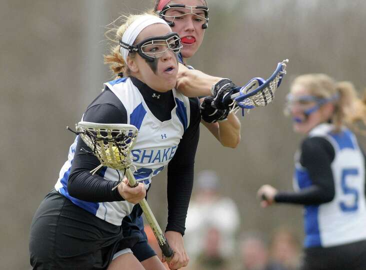 Shaker High School girls lacrosse player Maddie Devine, left, makes a run at the goal for a score du
