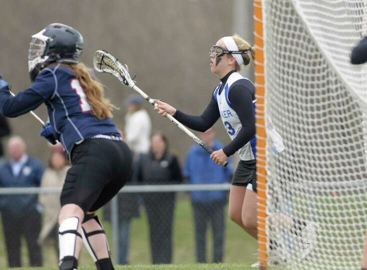 Shaker High School girls lacrosse player Maddie Devine, right, comes around the back of the cage loo