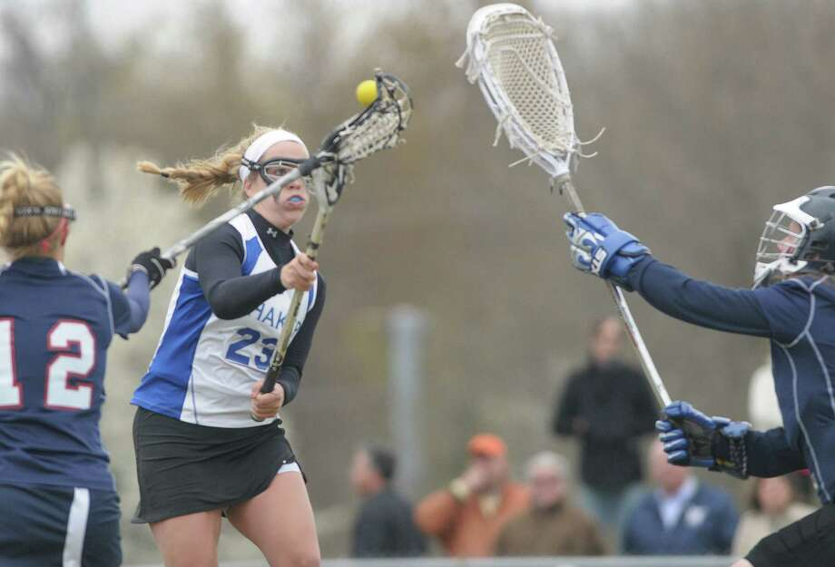 Shaker High School girls lacrosse player Maddie Devine, center,  takes a shot on goal and scores during their game against Saratoga Springs High School on Tuesday, April 10, 2012 in Latham, NY.   (Paul Buckowski / Times Union) Photo: Paul Buckowski