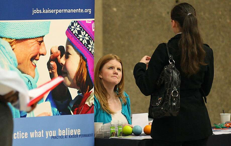 A recruiter, left, talks with a person searching for a job during a job fair Tuesday, April 10, 2012, in Gresham, Ore. Employers posted slightly more job openings and stepped up overall hiring in February. The figures suggest that modest job gains may continue in the coming months. (AP Photo/Rick Bowmer) Photo: Rick Bowmer, Associated Press