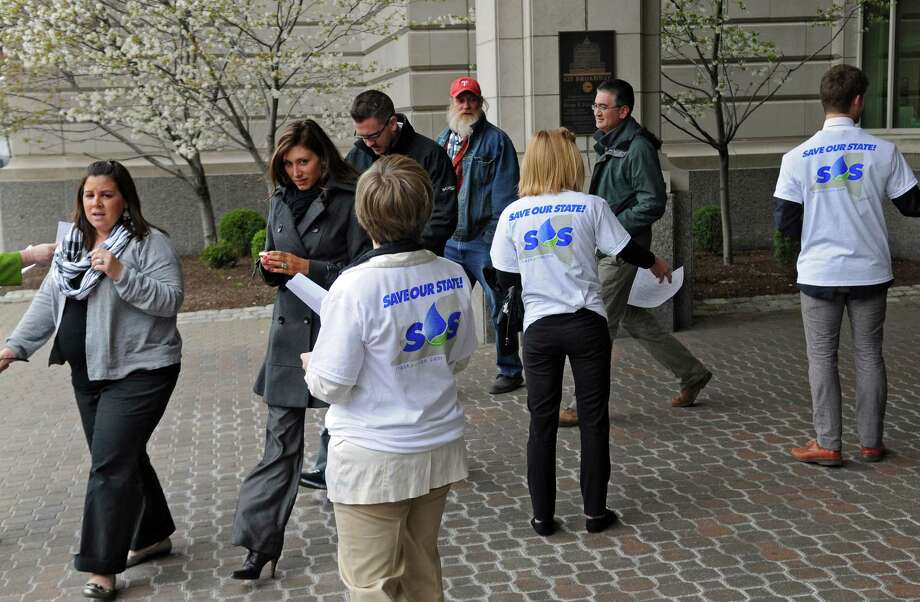 Anti fracking protesters hand out literature to people emerging from the NY State Department of Environmental Conservation headquarters, calling on employees to come out as whistleblowers against fracking, on Tuesday April 10, 2012 in Albany, NY.  (Philip Kamrass / Times Union ) Photo: Philip Kamrass / 00017118A