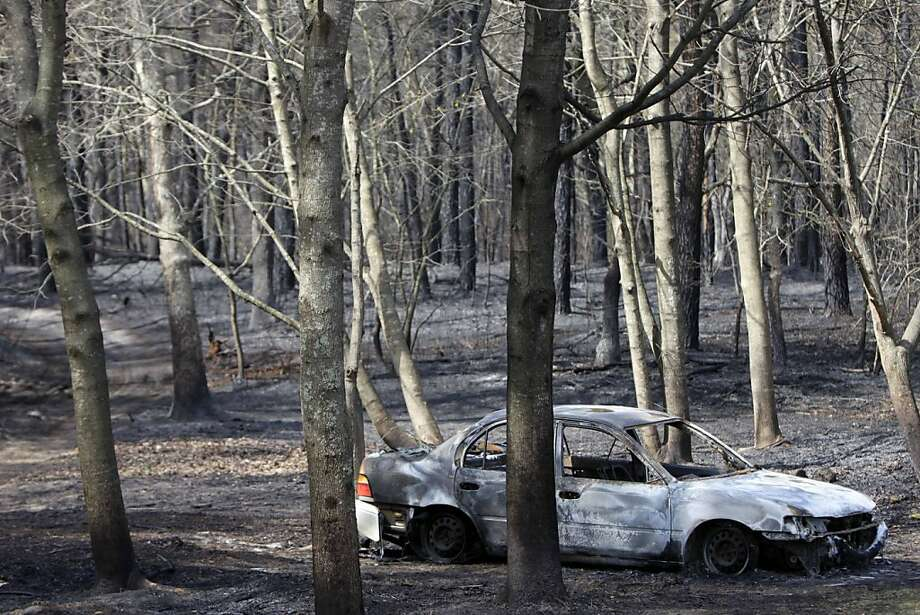 The remains of a charred car sits in the woods where a brush fire burned near Manorville, N.Y., Tuesday, April 10, 2012.  The fire, which destroyed three homes and a commercial building and burned about 1,000 acres on eastern Long Island, was nearly contained Tuesday, but officials warned that high winds could make the blaze unpredictable. (AP Photo/Seth Wenig) Photo: Seth Wenig, Associated Press