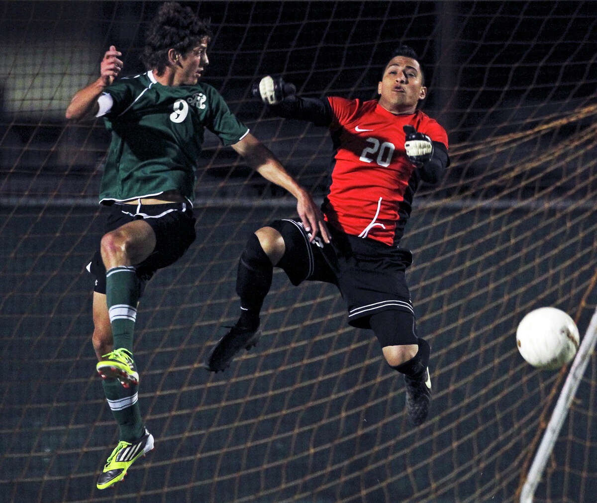 Southwest goalkeeper Daniel Huerta deflects the ball on a scoring try by Reagan's Juan Pablo Garza as the Dragons take on the Rattlers in the playoffs at Blossom Soccer Stadium on Tuesday, April 10, 2012.