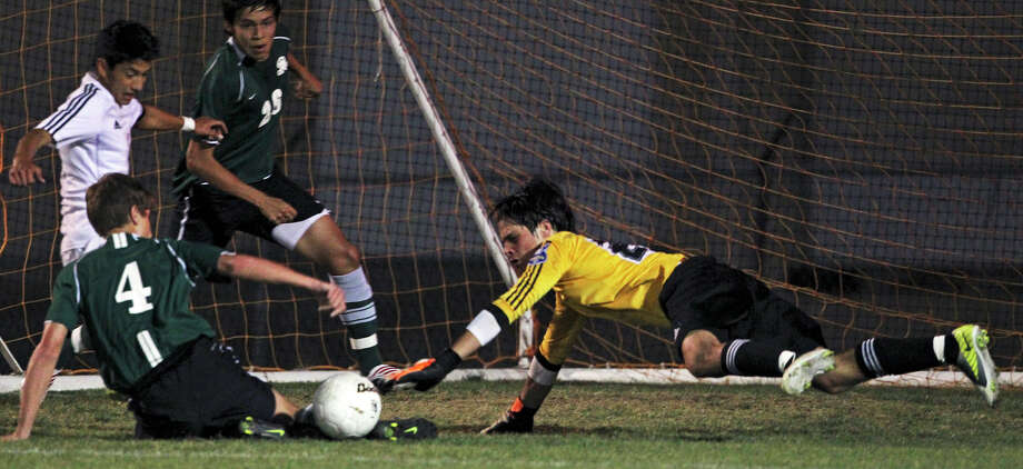 Reagan goalkeeper Andres Hernandez scrambles to stop a threat on goal as the Dragons take on the Rattlers in the playoffs at Blossom Soccer Stadium on Tuesday, April 10, 2012. Photo: TOM REEL, San Antonio Express-News / San Antonio Express-News